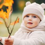 Cute little girl in a autumn park. Child in a white jacket and white hat
